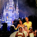 Talk show host Tyra Banks with a bevy of Princess Tianas in front of an irredescent castle at the Magic Kingdom.