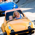 Playboy Playmate Jenny McCarthy in the passenger seat of an Autopia car at Disneyland.