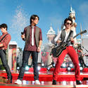 The Jonas Brothers perform during a Christmas special in front of Sleeping Beauty Castle at Disneyland.