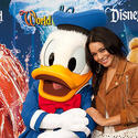 """High School Musical"" star Vanessa Hudgens arm in arm with Donald Duck at Disneyland."