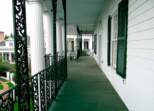 A second-story porch with hand-welded iron railings adorns the replica Haunted Mansion outside Atlanta.