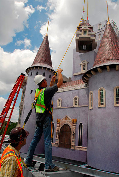 "Construction crews apply the finishing touches to a forced-perspective castle in the ""Beauty and the Beast"" section of the Fantasyland expansion at the Magic Kingdom."