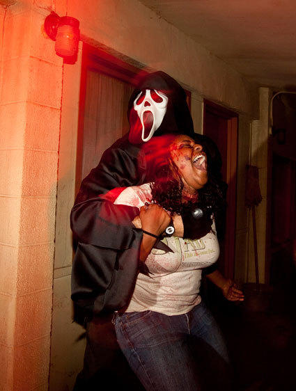 A Ghostface killer holds a victim at knifepoint leading up to the Scream maze at Halloween Horror Nights.