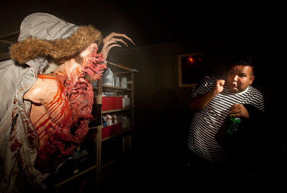 An alien in a fur-lined parka leaps at a terrified visitor at Halloween Horror Nights.