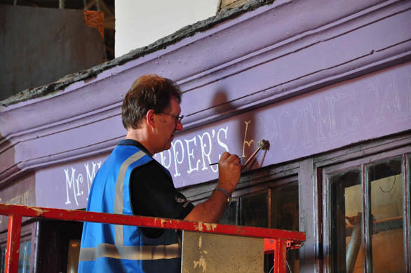 A Thinkwell Group scenic artist paints a sign on Mr. Mulpepper's Apothecary shop on Diagon Alley at the Making of Harry Potter tour at Warner Bros.' studios in England.