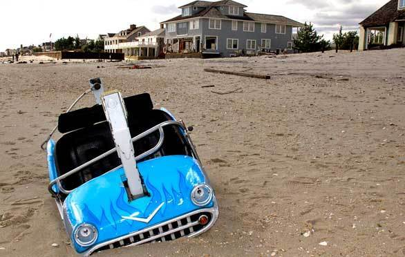A car from an amusement park on the Seaside Heights, N.J., boardwalk is partly buried in the sand at Mantoloking, about eight miles to the north.
