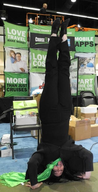 Some people flip for the Travel Show. Mathy Wasserman of Cruise Planners does a headstand while the finishing touches go on that company's booth.