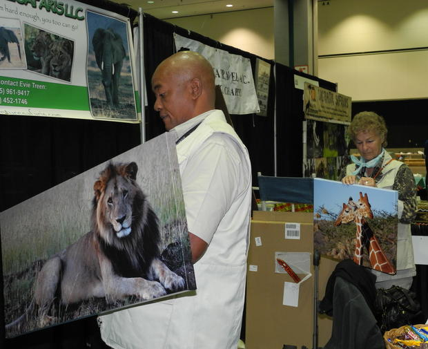 William Muli and Evie Treen of Vision Adventure Safaris hang photos that Treen has shot on her many trips to Tanzania and Kenya, the countries in which Vision Adventure specializes.