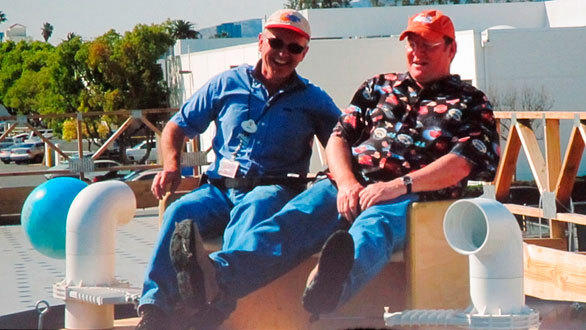 "Pixar chief and Disney Imagineering advisor John Lasseter, right, takes a ""play test"" ride on a prototype for Luigi's Flying Tires."