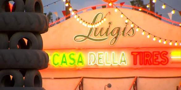 The Casa Della Tires neon sign glows next to a leaning tower of tires in Cars Land at Disney California Adventure.