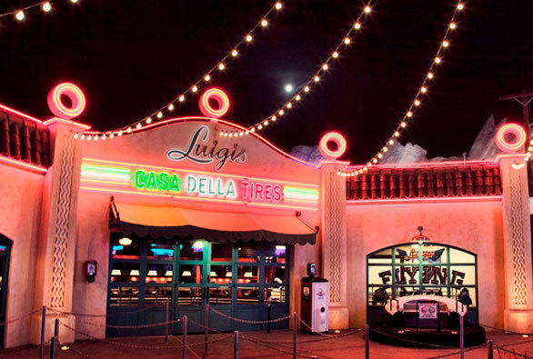 The neon trim of Luigi's Casa Della Tires lights up at night in Cars Land at Disney California Adventure.