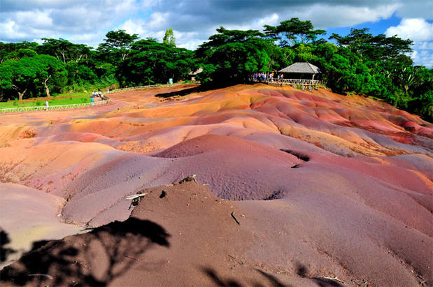 "Check out the multicolored rolling dunes known as colored earths in Chamarel on the western side of Mauritius, an island nation off the southeastern coast of Africa. The blue, brown, green, orange, purple, red and yellow patterns were formed when volcanic rocks cooled at different temperatures. Rain eventually carved the patterns into an undulating landscape. This strange bit of nature is best seen in the early morning or evening for the best contrasts in the hills and the vegetation in the background. Nearby, the Chamarel Falls can be seen plunging hundreds of feet. <a href=""/travel/deals/la-trb-offbeat-colored-earth-photos,5157123,4691454.photogallery""><span style=""color: #2262CC;"">More photos...</span></a>"