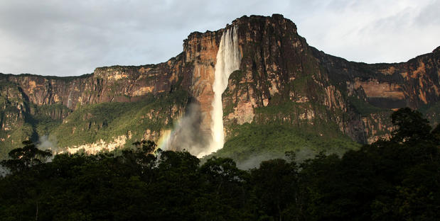 "Angel Falls, the world's highest waterfall plunges 3,212 feet from the top of Auyan-Tepui (Devil's Mountain) to the Churun River in eastern Venezuela. The waterfall, located in Canaima National Park, is named after James Angel, an American aviator who flew over the falls in 1933. <a href=""http://www.latimes.com/travel/deals/la-trb-offbeat-traveler-angel-falls-20110811,0,3786141.photogallery"" style=""color: 2262cc;"">More photos...</a>"
