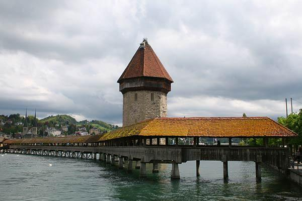 "Despite centuries of wear and even a fire, Europe's oldest wooden bridge continues to charm tourists in Lucerne, Switzerland. The Chapel Bridge, which cuts diagonally across the Reuss River, was built in the early 14th century. About 300 years later, the bridge was adorned with a series of triangular paintings depicting events in the city's history. In 1993, fire nearly destroyed the bridge. It was largely restored in 1994. <a href=""/travel/deals/la-trb-offbeat-traveler-chapel-bridge-in-lucerne-20120507,0,1968092.photogallery""><span style=""color: #2262CC;"">More photos...</span></a>"