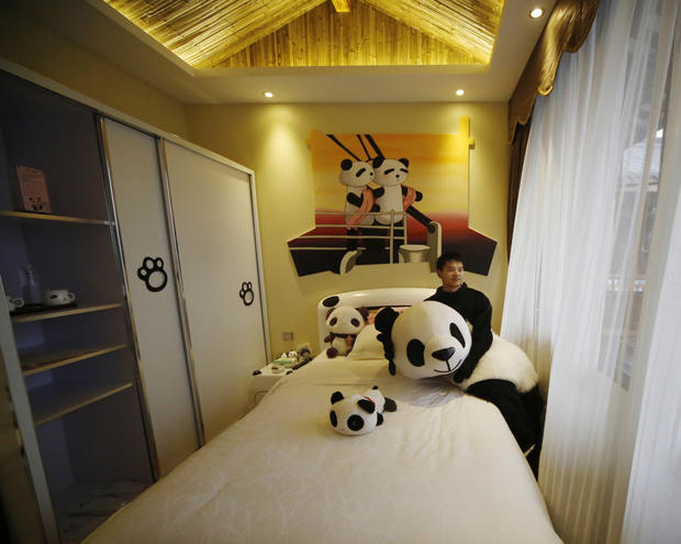 A staff member sits on the bed of a mini room at the Panda Inn.