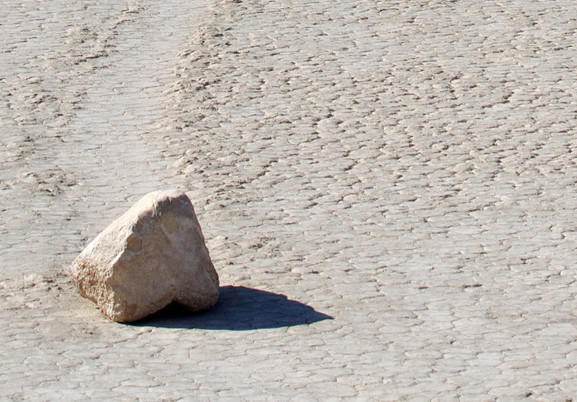 A large, nose-shaped rock rests on the playa.