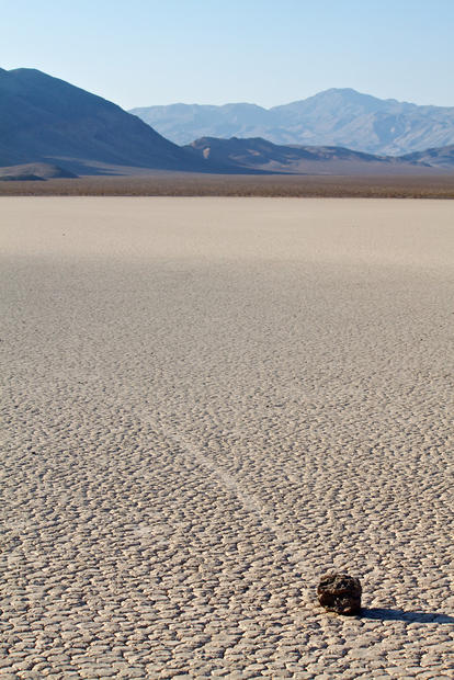 A rock leaves a trail behind it as it slowly makes its away across the playa. The pattern of the playa's surface is formed from hexagon-shaped cracks in the mud.
