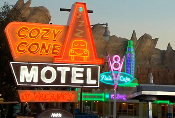 The Cozy Cone Motel neon sign glows in the foreground of Cars Land at Disney California Adventure.