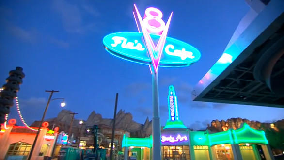 The Flo's V8 Cafe neon sign glows in the foreground of Cars Land at Disney California Adventure.