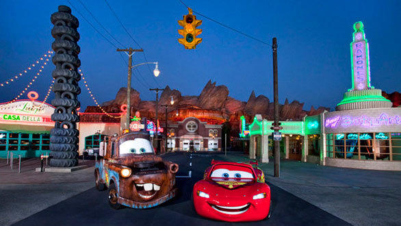 Lightning McQueen and Mater greet visitors amid the neon lights of Cars Land at Disney California Adventure.