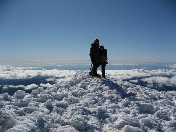 These two hikers, who look as if they're floating on clouds, stand atop snow-covered Mt. Hood.