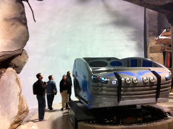 Visitors on the behind-the-scenes tour of the Transformers ride at Universal Studios Hollywood are dwarfed by a ride vehicle and the towering screen.