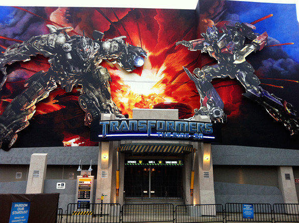 Out front, a towering portrait of Optimus Prime and Megatron in mid-battle hangs over the main entrance of the Transformers ride at Universal Studios Hollywood.