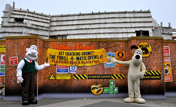 The Wallace & Gromit walk-around characters stand in front of construction walls surrounding the Thrill-O-Matic dark ride coming to Blackpool Pleasure Beach.