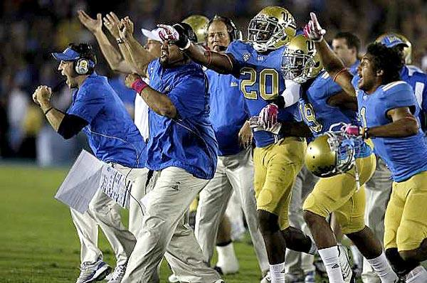 UCLA players and coaches react as the Bruins defense makes a key stop against California in the fourth quarter Saturday night at the Rose Bowl in a 31-14 victory.