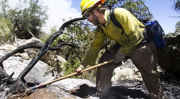 Ian Johnson, a Bureau of Land Management firefighter, mops up hot spots as a wildfire burns in the Bradshaw Mountains in Arizona's Prescott National Forest. The Gladiator fire, according to InciWeb, began May 13 near Crown King, Ariz., and then moved into the Prescott National Forest.