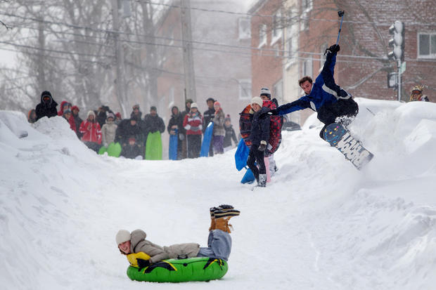 A snowboarder catches air as some more carefree Bostonians take to a snow-covered hill for winter sports fun.