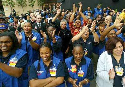 Wal-Mart employees cheer as they await the grand opening of the Baldwin Hills Crenshaw Plaza store on January 22, 2003.