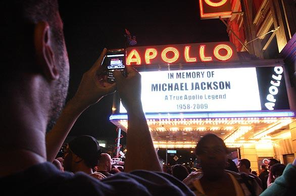"Tshaka Lafayette takes a picture of the marquee at the Apollo Theater as people  gather to remember Michael Jackson in the Harlem neighborhood of New York. ""I'm trying to capture a piece of American history,"" said Lafayette."