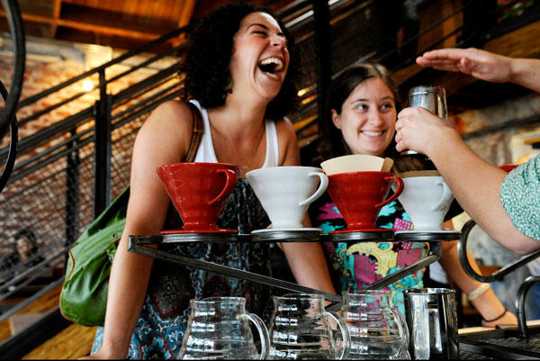 Linda Rosenblatt, left, and Sara Leiv joke around with one of the baristas at the newly opened Paper or Plastik Cafe in Pico Village.