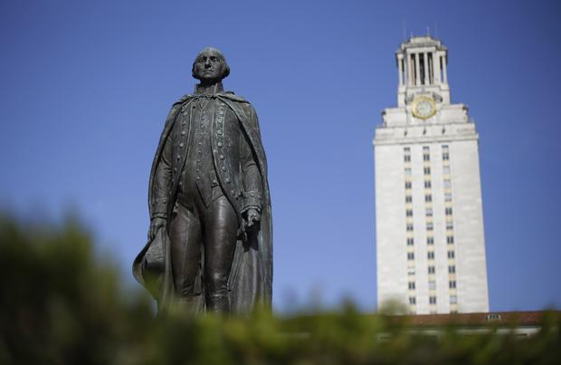 A statue of George Washington rises near the University of Texas Tower in Austin.