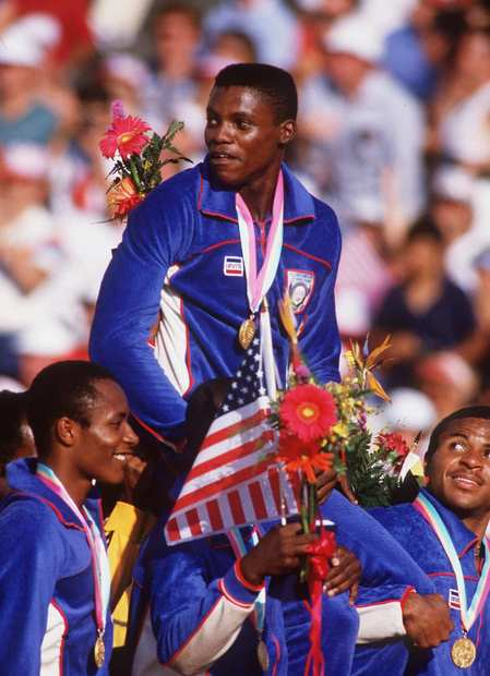 With a gold medal around his neck, Carl Lewis rides on the shoulders of his 400-meter relay teammates after the medal ceremony at L.A.'s Coliseum. The win made it four golds for Lewis at the 1984 Games.