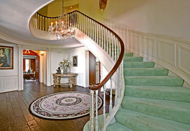 The shipshape home's foyer includes a grand sweeping staircase.