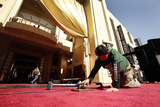 Daniel Velasquez, works on the last sections of red carpet at the entrance to the Hollywood & Highland Center.