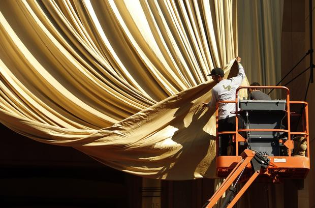 Riggers David Eno, left, and Chris Roseli, right, work to dress the giant gold curtain for Sunday's Oscar telecast.