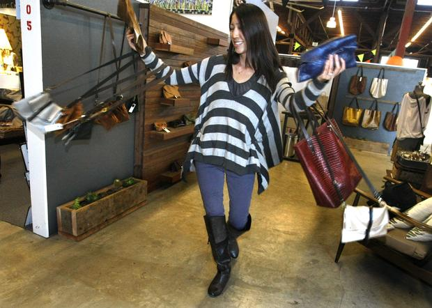 Teresa Cheung, 34, owner and designer of Salvageshop, walks through her booth with some of the leather purses, totes and clutches she made from leather remnants. Cheung recently lost her job as an architect but says this enabled her to realize her longtime desire to start her own business.