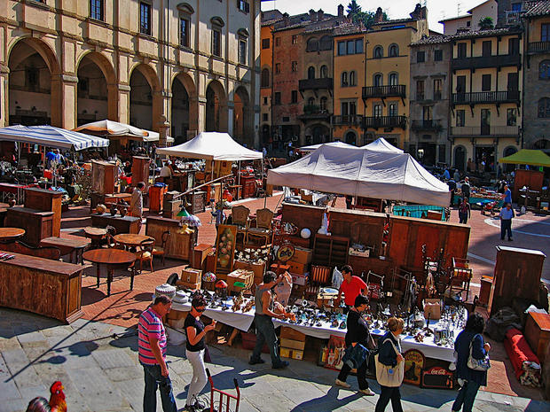 "The Arezzo antiques fair, Italy's oldest and largest, takes place the weekend that includes the first Sunday of each month, just 40 miles from Florence. With 500 sellers from Calabria to Campania, Padua to Pistoia, merchandise fills the piazza, climbs up the hill to the cathedral and spills down the side streets past the Chiesa di San Francesco, home to Piero della Francesca's masterwork frescoes, ""The Legend of the True Cross."" The jewel-toned frescoes are reason enough to visit Arezzo.<br /><br />  Most items at the fair are from the 19th and early 20th century, but you can find treasures. A 15th century illustrated hymnal is not the memento for me, but it's in fine condition, pages intact. A few steps away I admire a beautiful replica of a 17th century Venetian intaglio dining table with three leaves, for $2,100. <br /><br />  -- Laura Deutsch<br /><br />  Read more: <a href=""/travel/la-tr-arezzo-20100328,0,5275985.story"">Antique-hunting in Arezzo, Italy</a>"