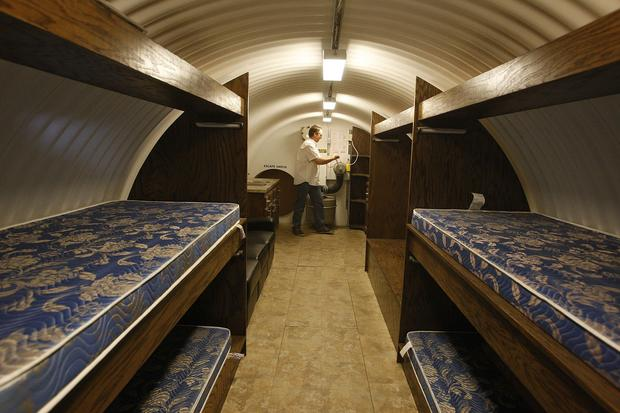 Ron Hubbard demonstrates how to manually pump air into a 25-foot underground shelter with five beds. The shelter has been upgraded with an oak interior finish.