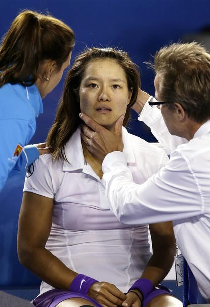 Li Na is checked by a doctor after hitting her head on the court when she fell after rolling her left ankle for a second time in the Australian Open final.