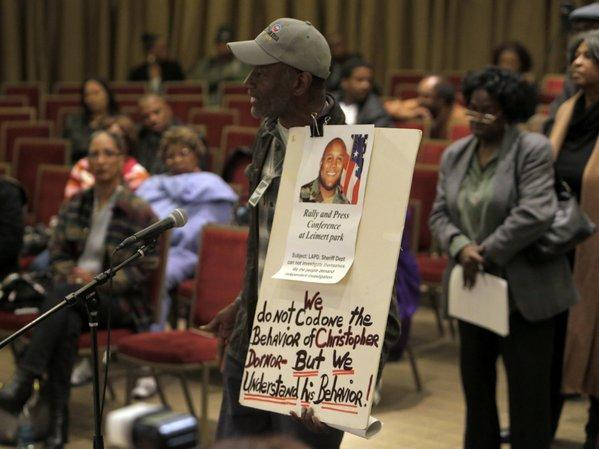 Community activist Morris Griffin holds a sign that echoed sentiments among some audience members at a meeting with L.A. Police Chief Charlie Beck. The Southern California Cease Fire Committee hosted the forum with  Beck to address South L.A. residents' concerns about the LAPD and the late Christopher Dorner's manifesto, which blamed his firing from the department on racists and liars.