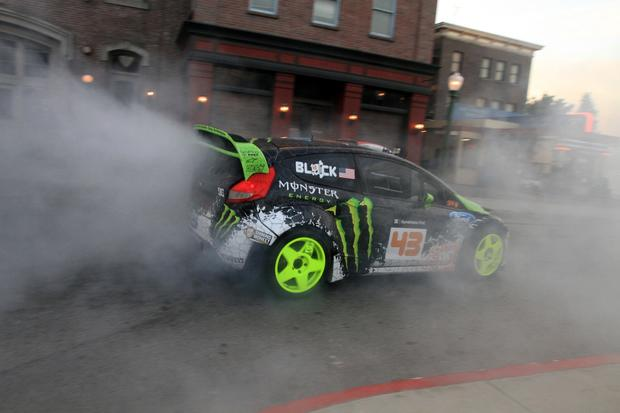 Stunt driver Ken Block drives around a Universal Studios lot in Los Angeles. After founding DC shoes and becoming a multimillionaire, Ken Block became a stunt driver. In one YouTube video, Block can be seen speeding down an empty Oakland Bay Bridge, ripping a set of tire-smoking doughnuts between two trolley cars, and seemingly breaking the laws of physics by twisting the car in mid-flight on a 90-degree turn after jumping a hill. Within 24 hours, the video was viewed more than 5 million times.