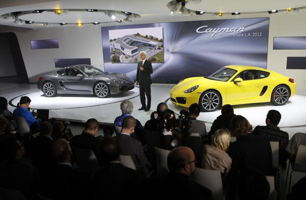 Matthias Muller, president and CEO of Porsche AG, introduces the new Cayman, left, and Cayman S, right, for its world debut at the L.A. Auto Show on November 28, 2012.