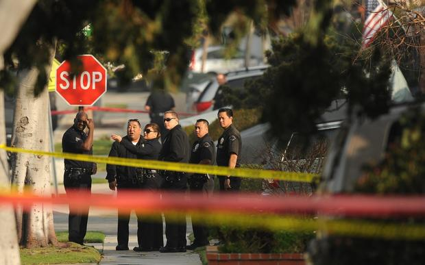 LAPD officers investigate after two women were shot by police while delivering newspapers Thursday morning in Torrance. The pickup truck the women were riding in is similar to the vehicle that multiple-homicide suspect Christopher Jordan Dorner is believed to be driving.