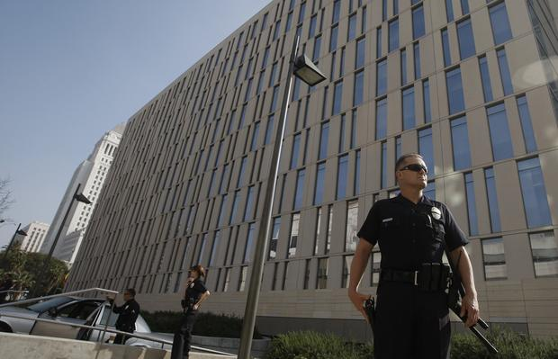 LAPD Officer Robert Paterson stands guard outside police headquarters in downtown Los Angeles as the department, operating on high alert, searches for an ex-officer suspected shooting three police officers, one fatally.