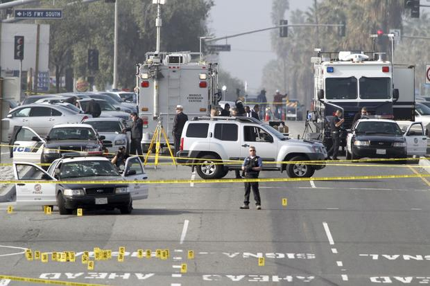 Police investagators look at the LAPD car, left , where an officer was wounded on Magnolia Avenue in Corona
