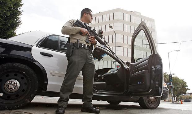 A Los Angeles County Sheriff's deputy guards the entrance to the Men's Central Jail and Twin Towers after reports that suspected gunman Christian Dorner had been seen in the area on Friday morning.
